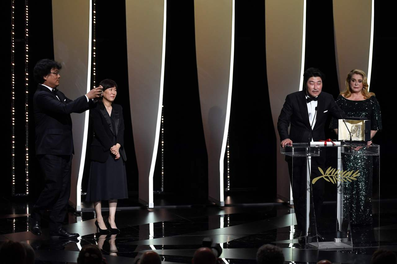 South Korean actor Song Kang-ho (2ndR) delivers a speech next to French actress Catherine Deneuve (R) after South Korean director Bong Joon-Ho (L) won the Palme d'Or for the film