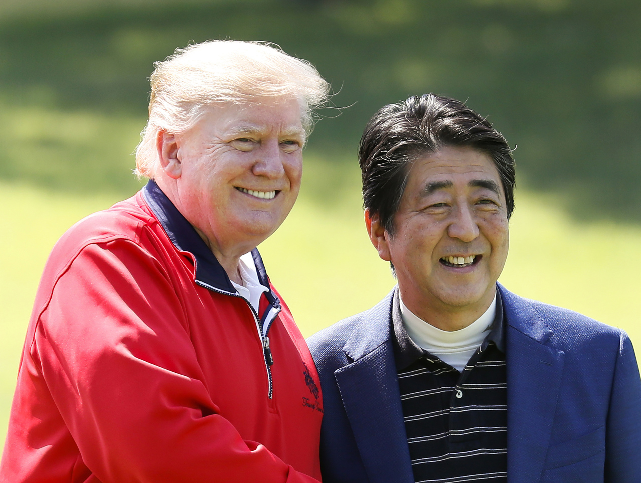 US President Donald Trump (left) and Japanese Prime Minister Shinzo Abe smile before playing a round of golf at Mobara Country Club in Mobara, south of Tokyo, Sunday. (AP-Yonhap)