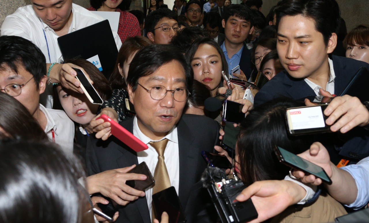 Yang Jung-chul, the head of the Institute for Democracy, is surrounded by reporters after a meeting at the National Assembly on Monday morning. (Yonhap)
