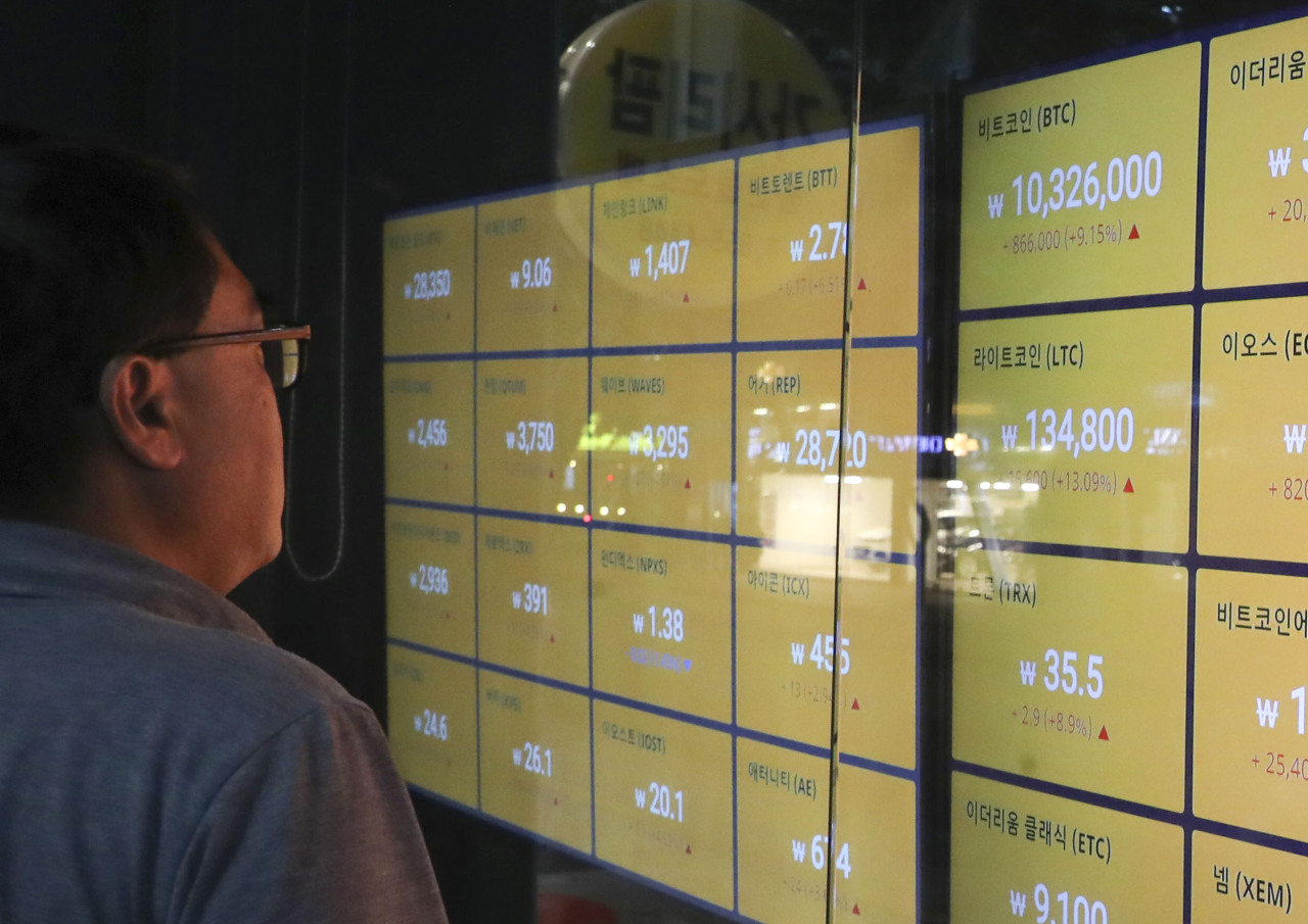 An investor looks at a screen that shows Bitcoin price index. Yonhap