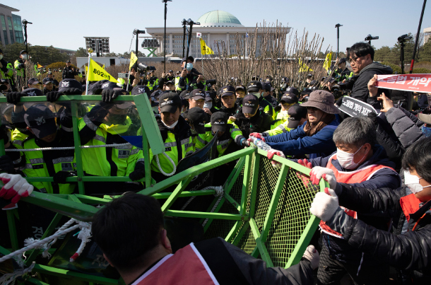 Members of the Korean Confederation of Trade Unions try to push their way into the National Assembly on April 3 in protest against the revision of flexible working hours and the minimum wage law. (Yonhap)