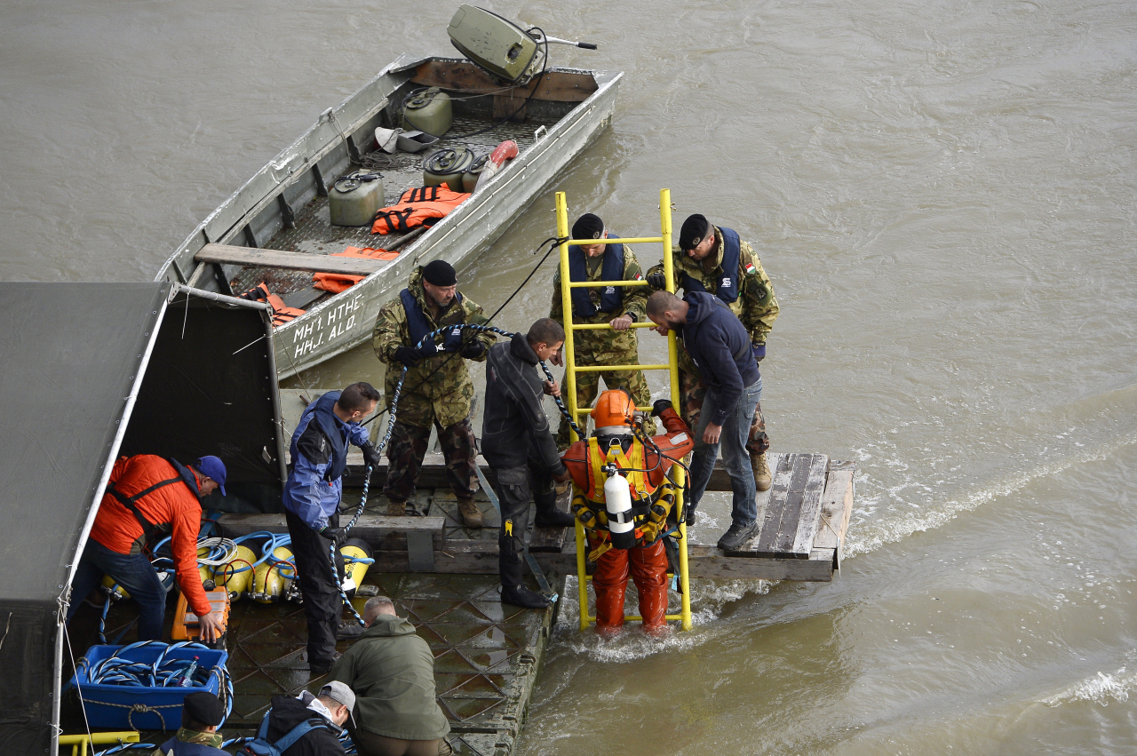 A diver descends a ladder to sink to the wreckage as rescuers work to prepare the recovery of the capsized boat under Margaret Bridge in Budapest, Hungary, 30 May 2019. A sightseeing boat carrying 33 South Korean tourists collided with a large river cruise ship on River Danube near the bridge last night, killing at least seven tourists. Seven tourists have been rescued, 21 persons, including the two crew members, have disappeared. (EPA-Yonhap)