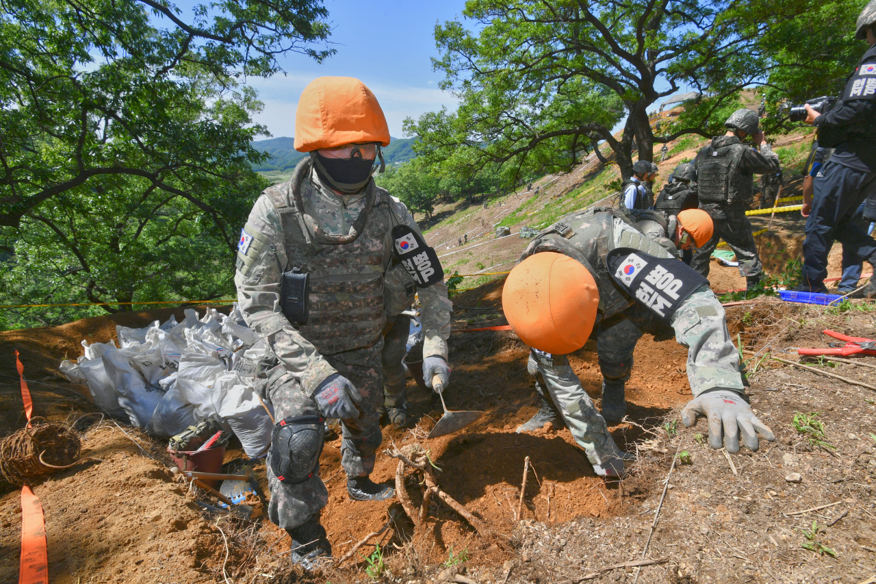 South Korean military personnel and officials from the war remains recovery agency MAKRI conduct excavation work at Arrowhead Ridge in the DMZ on Tuesday. (Yonhap)
