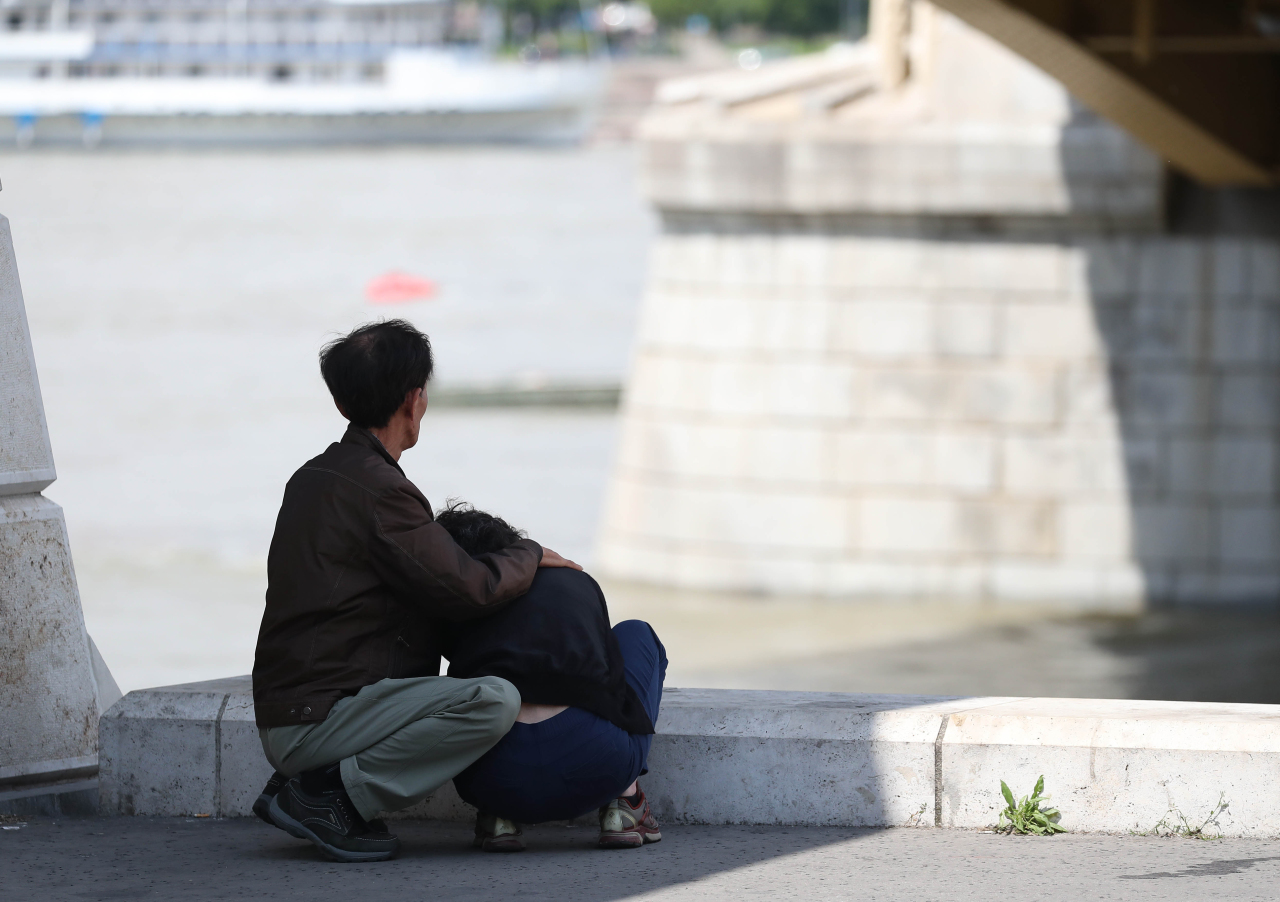 A berated family looks at the Danube river. (Yonhap)