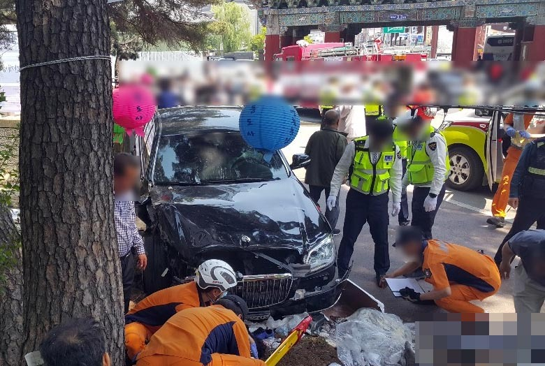Police and fire authorities examine a crash site that left two dead and 11 injured after a 75-year-old driver accidentally stepped on the accelerator pedal and drove into a crowd celebrating Buddha's Birthday at the temple Tongdosa in Yangsan, South Gyeongsang Province, on May 12. (Yonhap)