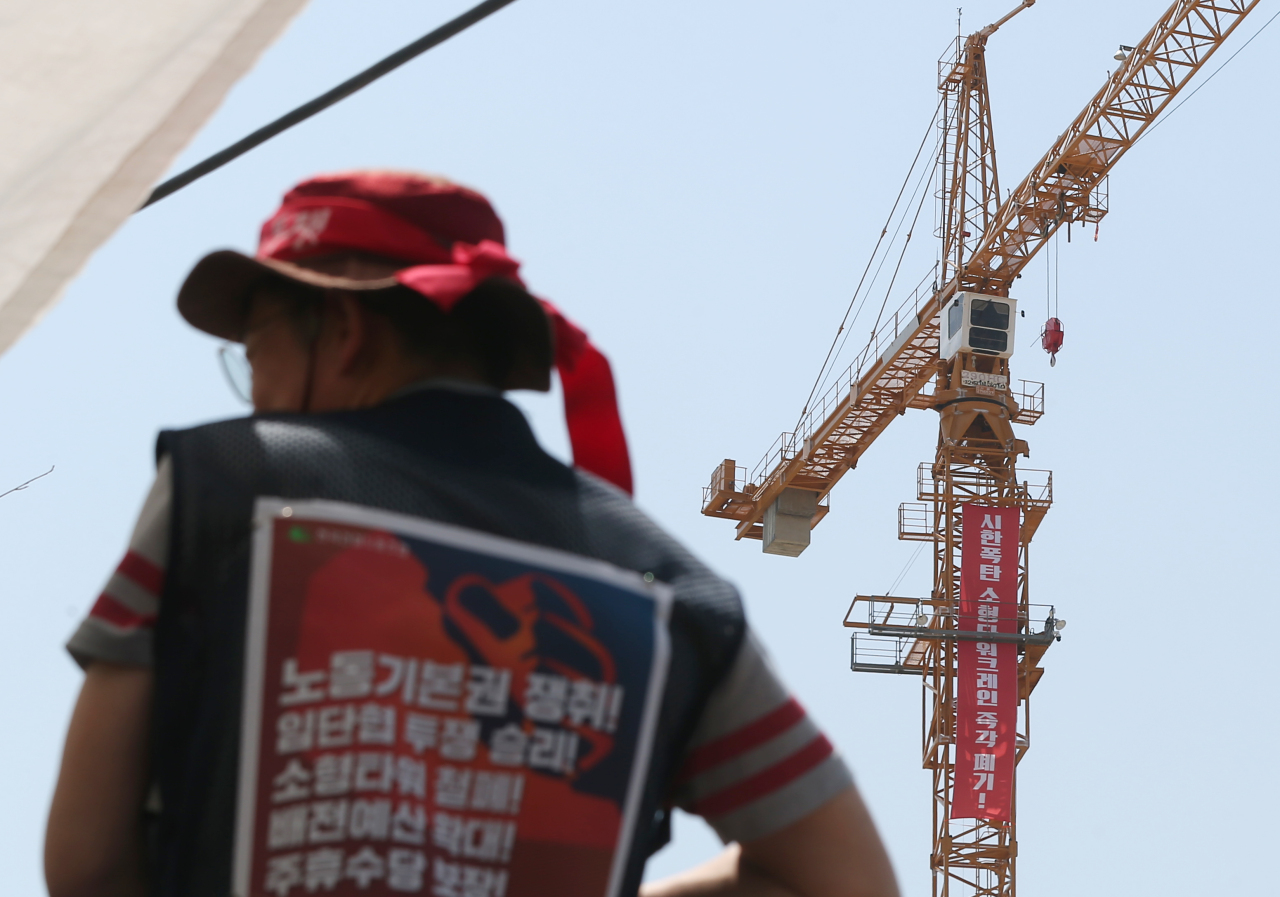 Striking tower crane workers stage a sit-in to protest the use of small tower cranes at an apartment construction site in Ulsan on Tuesday. (Yonhap)
