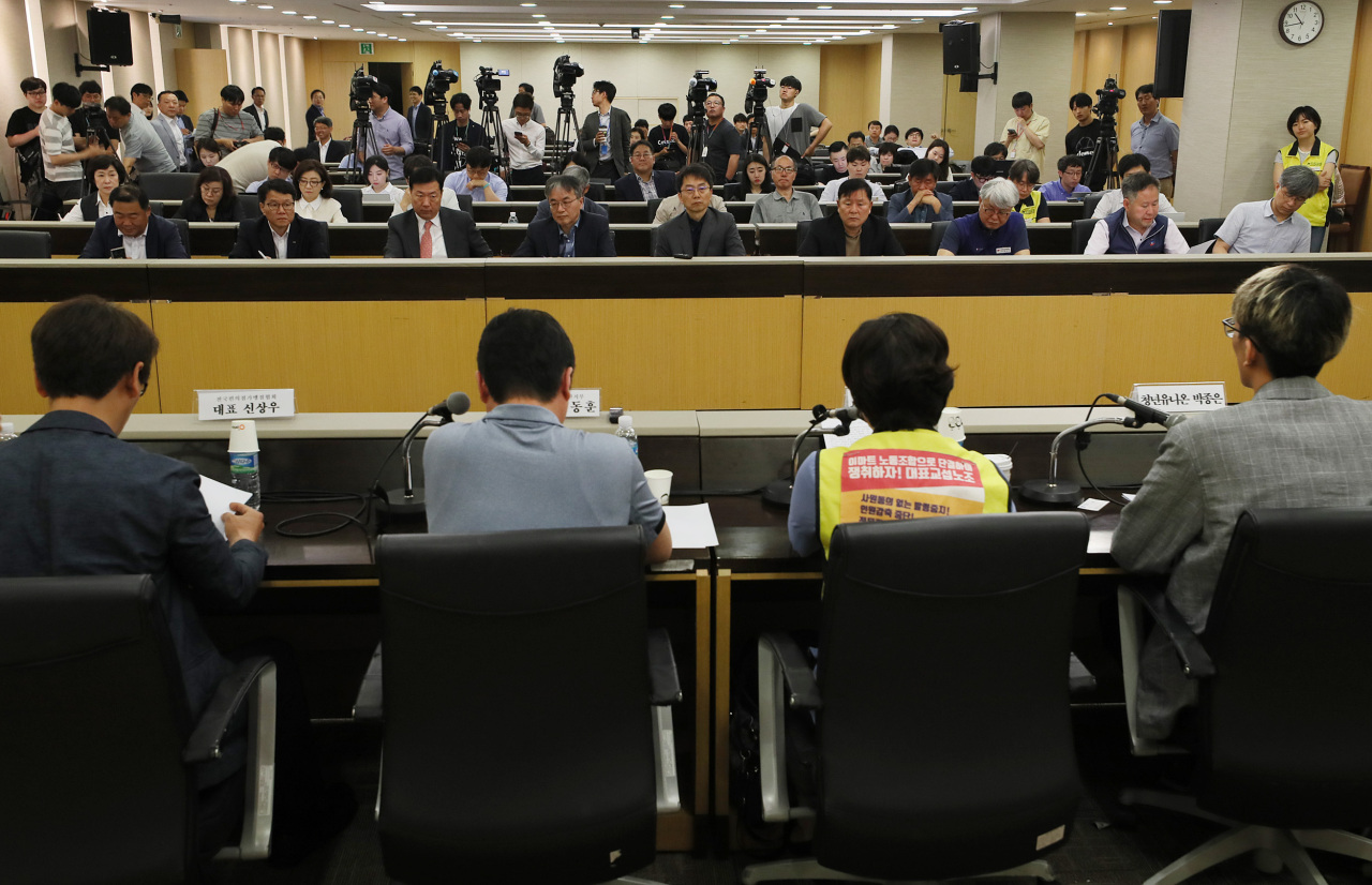 Minimum Wage Commission head Park Joon-sik (back row, center) attends a public hearing on next year's minimum hourly wage at the Labor Ministry's Seoul office on Wednesday. (Yonhap)