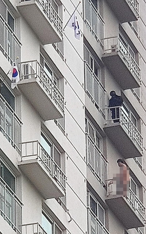 A man, 51, stands naked on the 12th-floor balcony of an apartment building in Uijeongbu, Gyeonggi Province, at around 7 a.m. Thursday. (Yonhap)