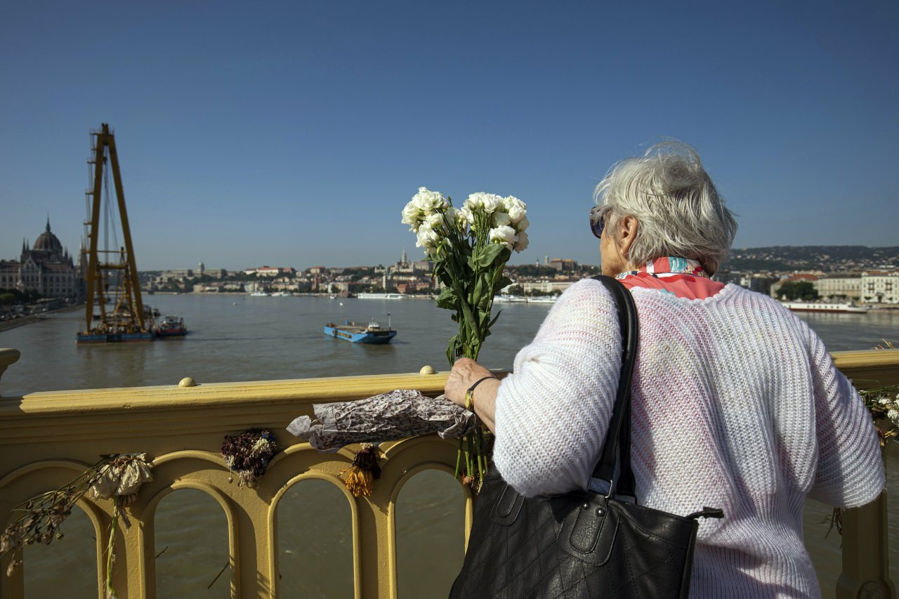 A woman holds a bunch of flowers Margaret Bridge, the scene of the deadly boat accident in Budapest, Hungary, Saturday, June 8, 2019. A sightseeing boat carrying 33 South Korean tourists was crashed by a large river cruise ship and sank in the River Danube on May 29. The body of seven tourists on board were retrieved on that night, seven tourists survived, 21 persons, including the two Hungarian crews went missing. Twelve more victims have been found and identified since then. (AP-Yonhap)