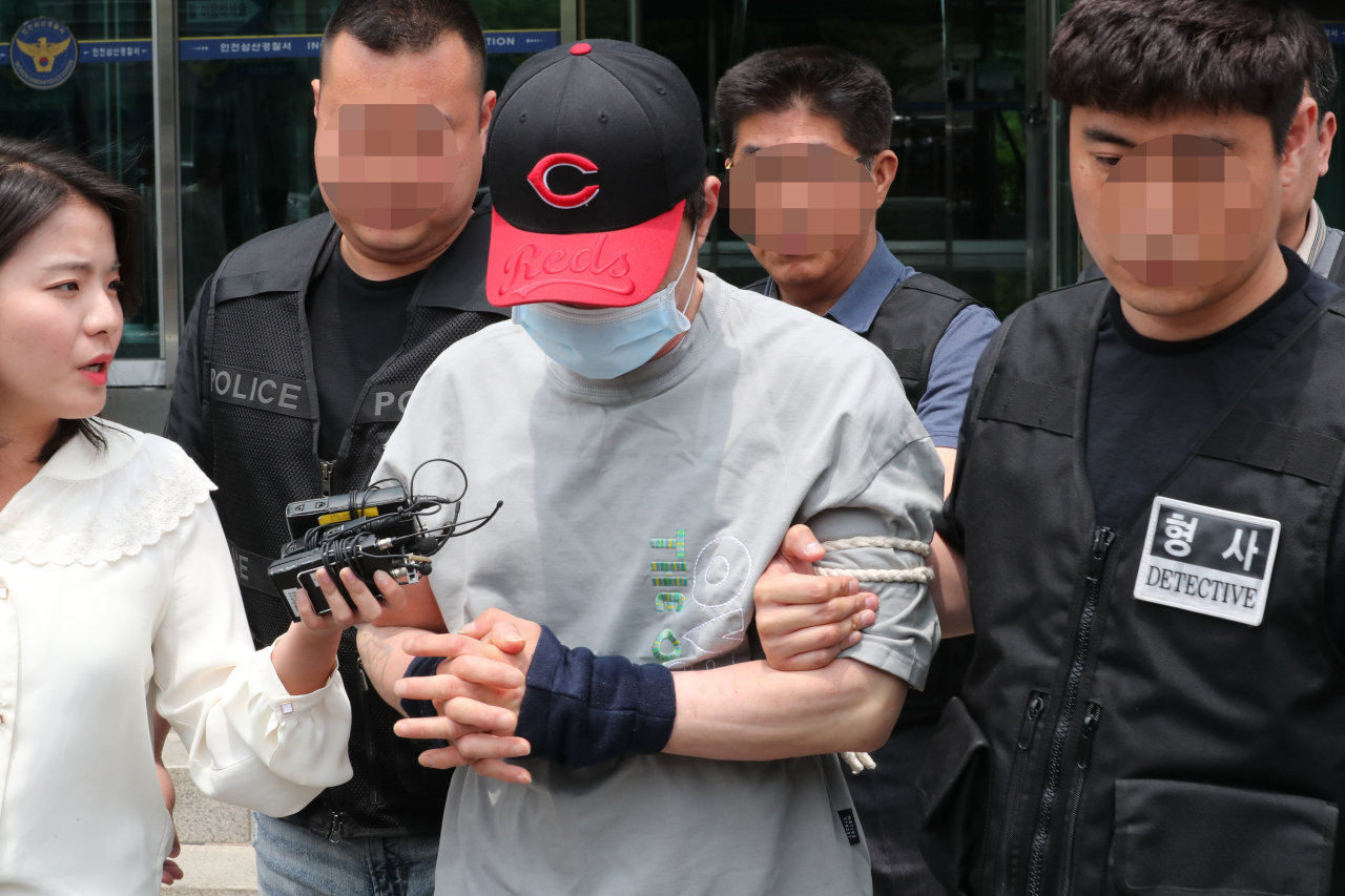 A man accused of stabbing his brother to death is seen leaving the Incheon Samsan Police Station for the Incheon District Court on Sunday. (Yonhap)