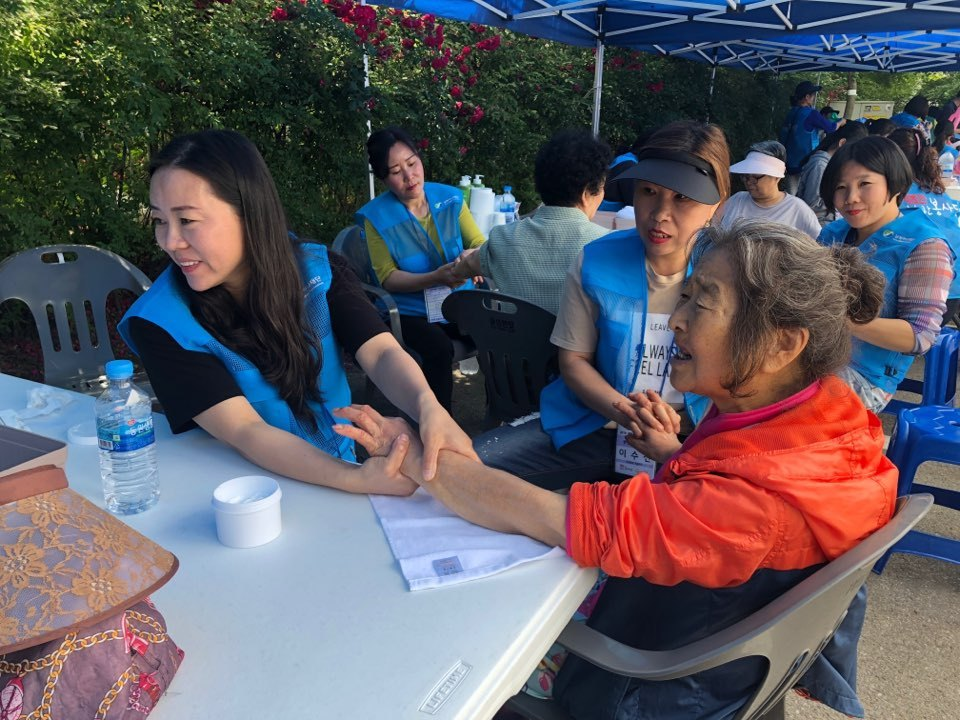 North Korean defector volunteers massage the hands of an elderly person in Paju, Gyeonggi Province, Saturday. (Jo He-rim/The Korea Herald)