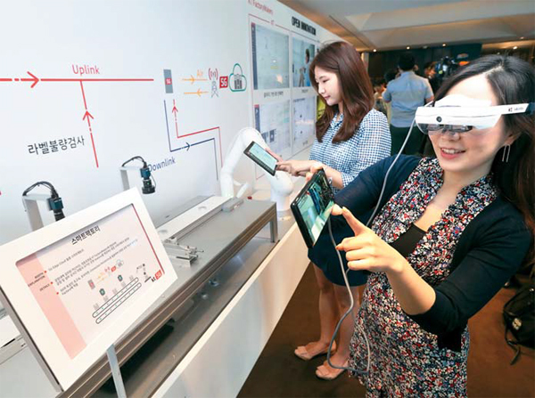 Visitors try out AR devices for KT`s 5G-powered smart factory. KT