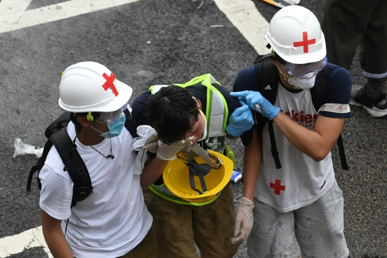 A protester is helped by medical volunteers after being hit by police tear gas -- officers were also hurt and health authorities said more than 70 people in total were injured, local broadcaster RTHK reported. (AFP)