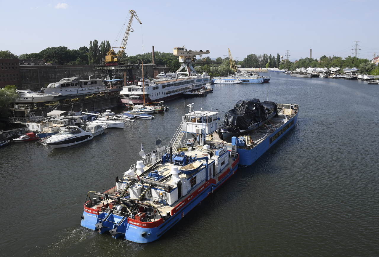 A barge arrives with the inspected wreckage of the Hableany sights eeing boat to a guarded dock in northern Budapest, Hungary, 13 June 2019, two days after the wreckage was salvaged from the riverbed. The boat carrying 33 South Korean tourists and two Hungarian staff was crashed by a large river cruise ship and sank in the River Danube on 29 May. Seven tourists survived, twenty-five people died, three persons are still missing. (EPA-Yonhap)