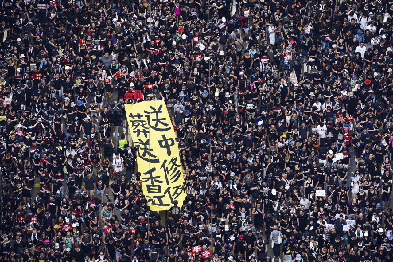 Tens of thousands of protesters carry posters and banners march through the streets as they continue to protest an extradition bill, Sunday, June 16, 2019, in Hong Kong. Hong Kong residents Sunday continued their massive protest over an unpopular extradition bill that has highlighted the territory`s apprehension about relations with mainland China, a week after the crisis brought as many as 1 million into the streets. The yellow banner reads