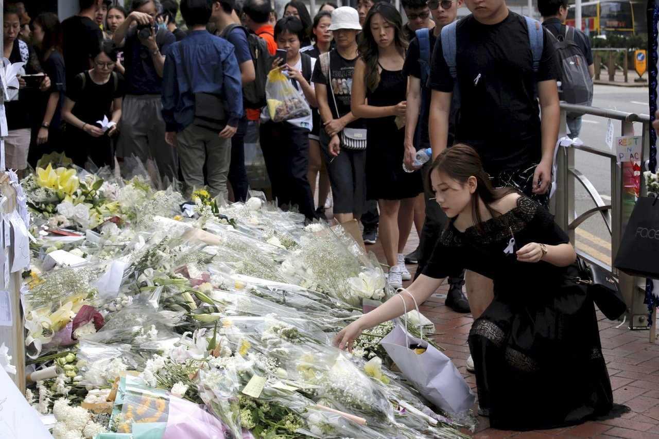 Mourners stop by a makeshift memorial, to lay flowers and pray for a man who fell to his death Saturday after hanging a protest banner against an extradition bill in Hong Kong Sunday, June 16, 2019. Tens of thousands of Hong Kong residents, mostly in black, have jammed the city's streets Sunday to protest the government's handling of a proposed extradition bill. (AP)
