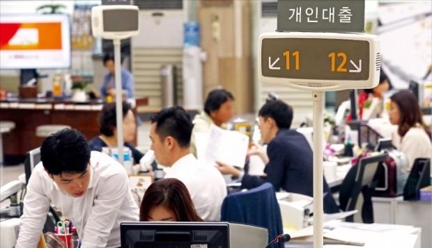 Tellers of a savings bank branch in Seoul serve customers. (Yonhap)
