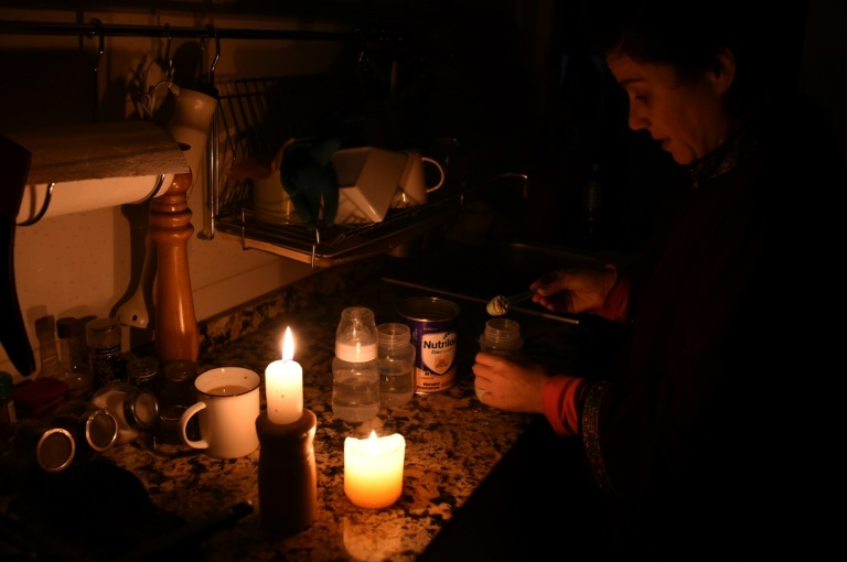 A woman prepares milk bottles by candle lights at her home in Montevideo during a massive power failure. (AFP)