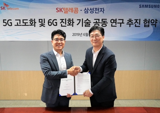 Jeon Jae-ho (R), head of network business R&D at Samsung Electronics Co., and Park Jin-hyo, the CEO of SK Telecom Co. (SKT)