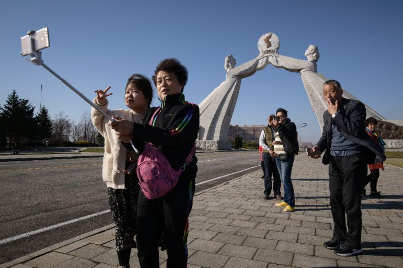 Tourists from China pose for photos before the Three Charters monument in the North Korean capital Pyongyang (AFP-Yonhap)