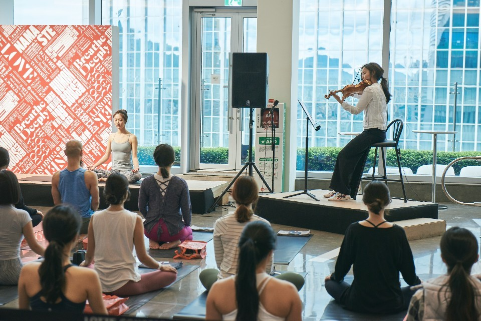 Violinist Lee Ji-yoon performs during a yoga class at the Lotte Concert Hall in April. (Lotte Concert Hall)