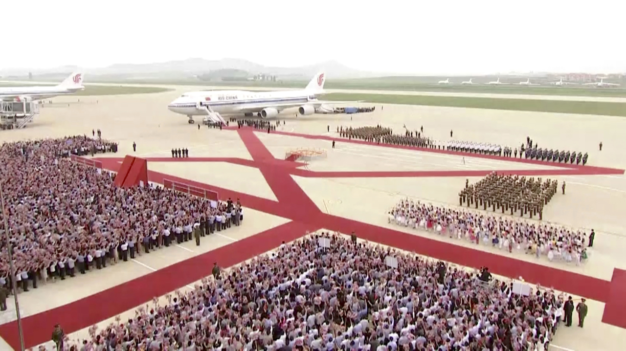 North Korean people and a guard of honor welcom e a plane with Chinese President Xi Jinping onboard, on the arrival at an airport in Pyongyang, Thursday. (AP-Yonhap)