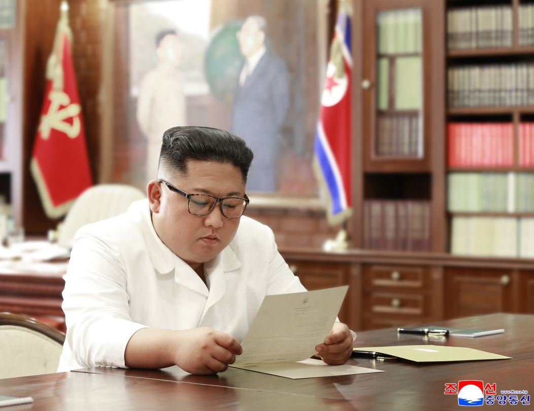 North Korean leader Kim Jong-un reads a letter from US President Donald Trump in his office in this picture released by the Korean Central News Agency on Sunday. (Yonhap-KCNA)