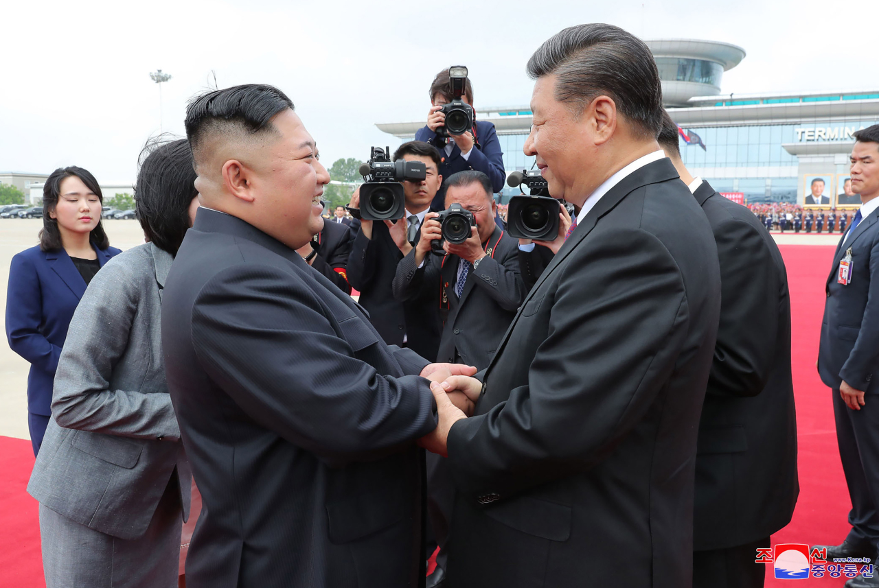 In this Friday, photo provided by the North Korean government, North Korean leader Kim Jong-un, (center left) and Chinese President Xi Jinping bid farewell at Pyongyang International Airport in Pyongyang, North Korea. (AP-Yonhap)