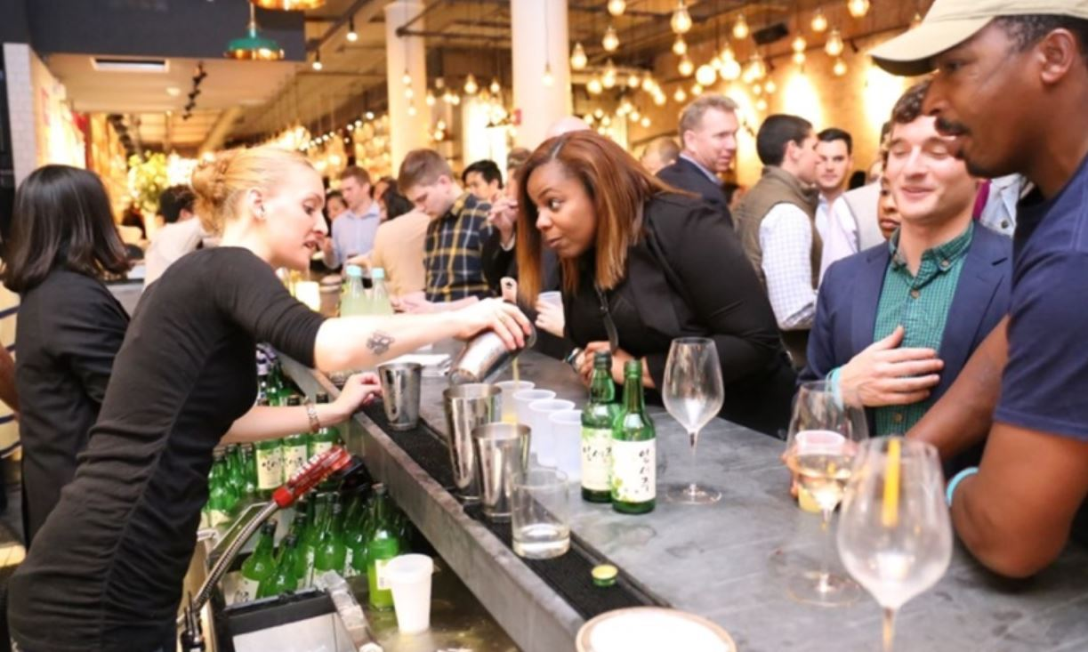 Promoters serve a brand of soju, a Korean traditional liquor made from dilution of spirits, to visitors to an international wine and food festival, held in New York. (Bohae)
