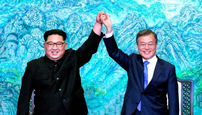 North Korean leader Kim Jong-un,(left) and South Korean President Moon Jae-in raise their hands after signing a joint statement at the border village of Panmunjom in the Demilitarized Zone, South Korea on April 27, 2018. (AP-Yonhap)
