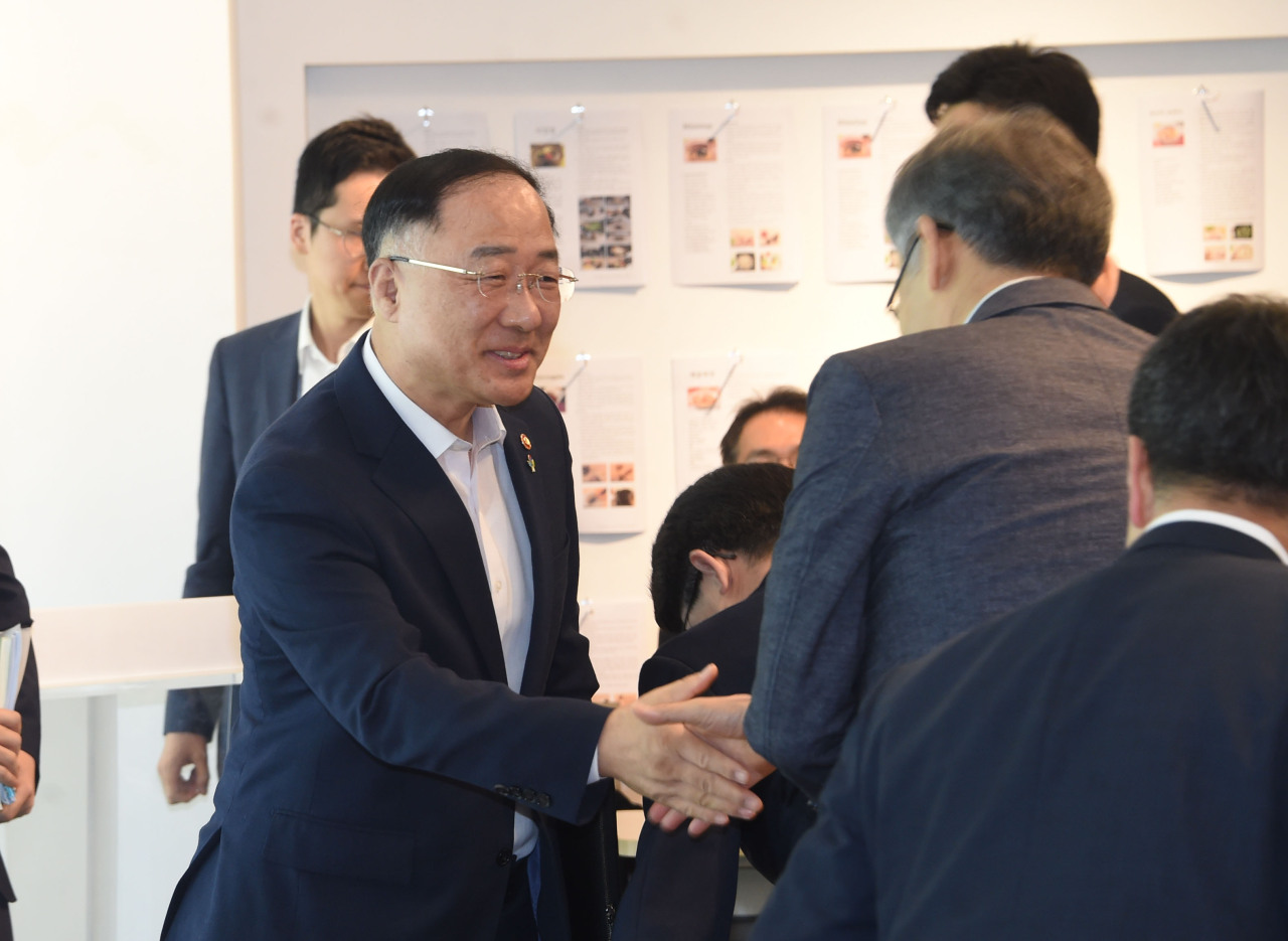 Deputy Prime Minister and Finance Minister Hong Nam-ki (left) attends a policy meeting at the Seoul office of the Korea Tourism Organization on Wednesday. (Ministry of Economy and Finance)