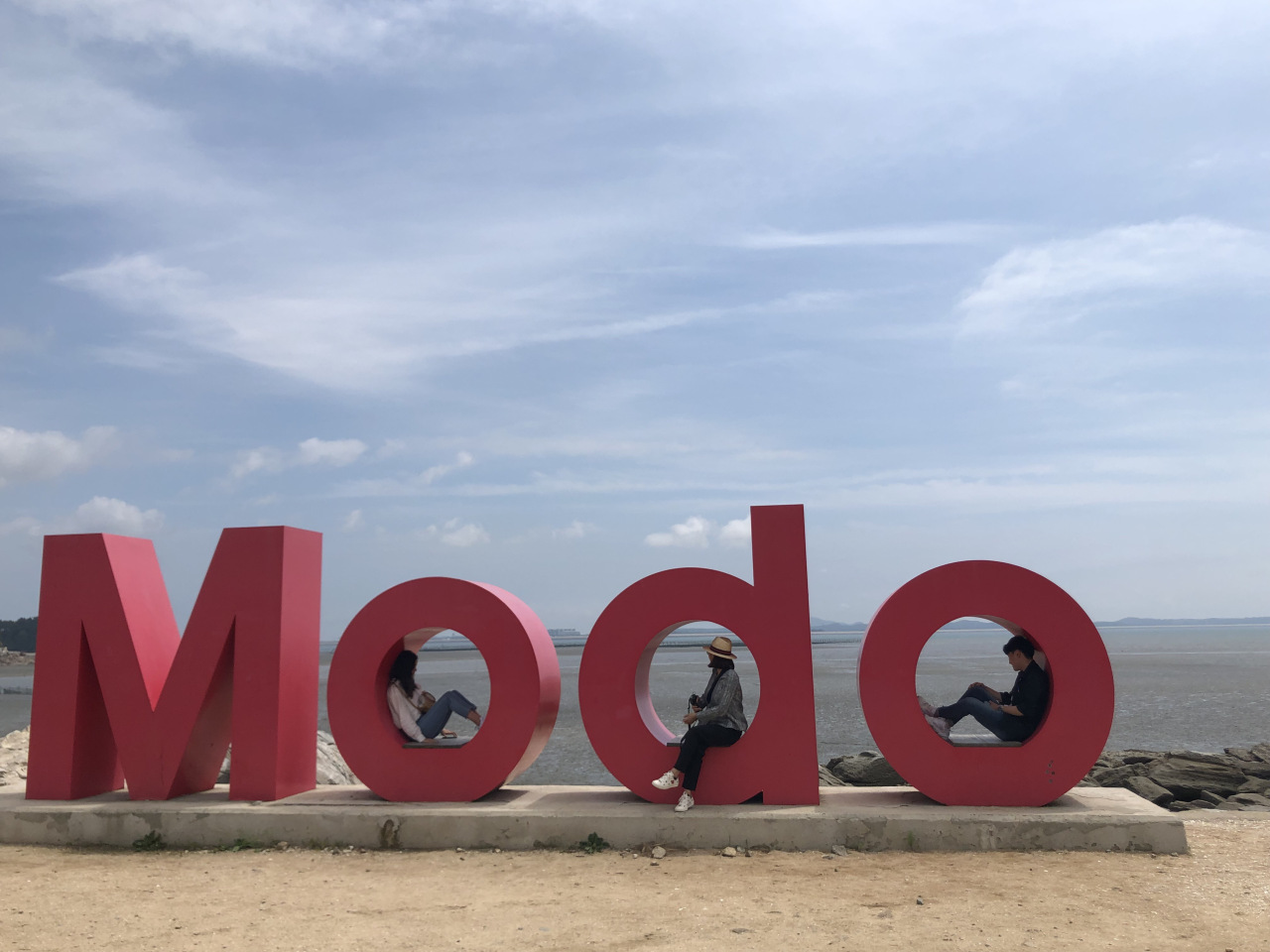 "Visitors pose on a three-dimensional sign that spells ""Modo"" on one of the island's beaches. (Paradise City)"