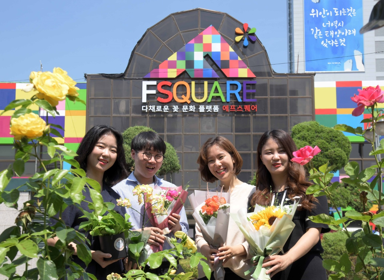 Employees pose at the rebranded flower business center F Square. (aT)