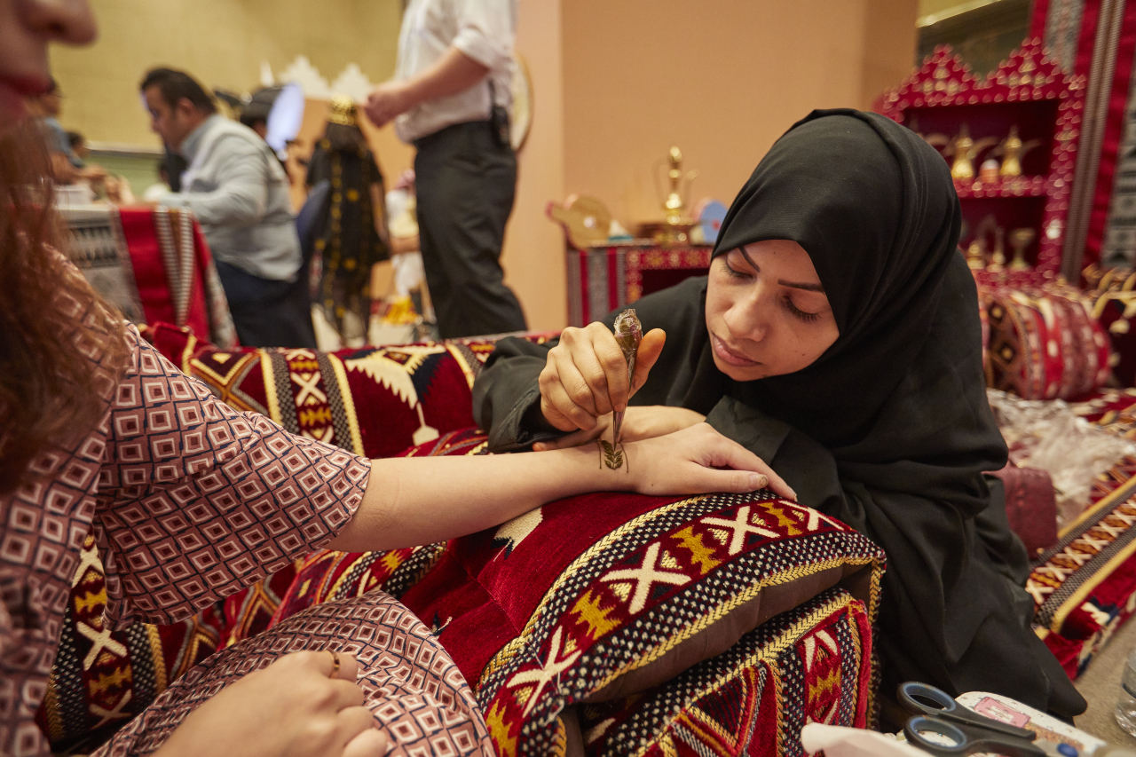 "A woman draws a henna tattoo on a visitor's hand during the ""Bridges to Seoul"" event at Grand Hilton Seoul. (The King Abdulaziz Center for World Culture)"