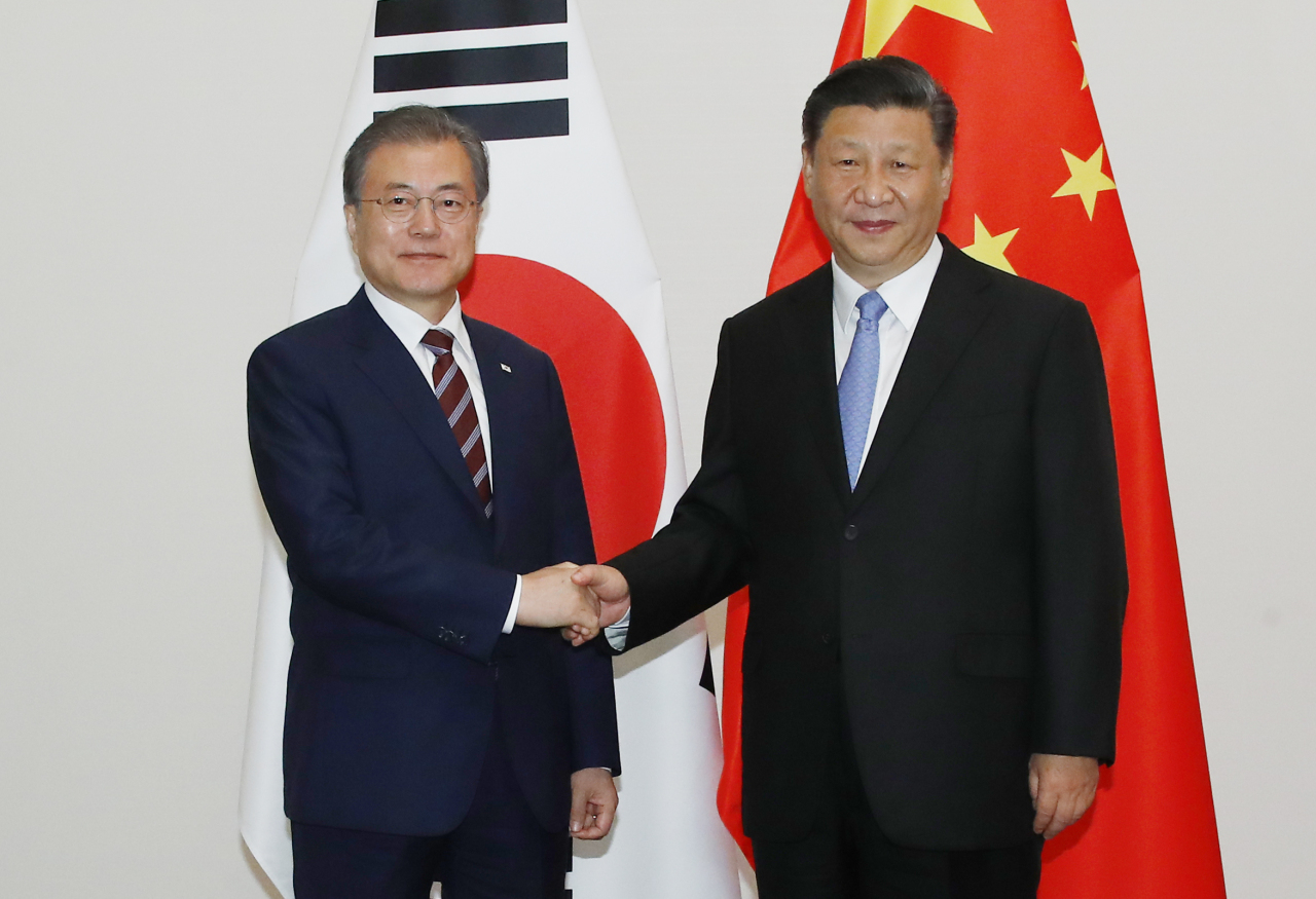 South Korean President Moon Jae-in (left) and Chinese President Xi Jinping shake hands during their summit in Osaka, Japan on Thursday. (Yonhap)