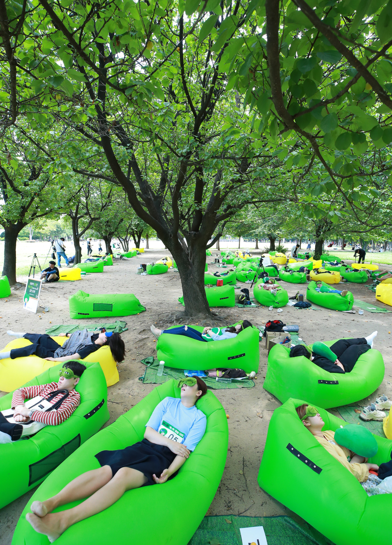 People lie down under the trees in Seoul Forest in Seoul's Seongdong district on Sunday, part of a