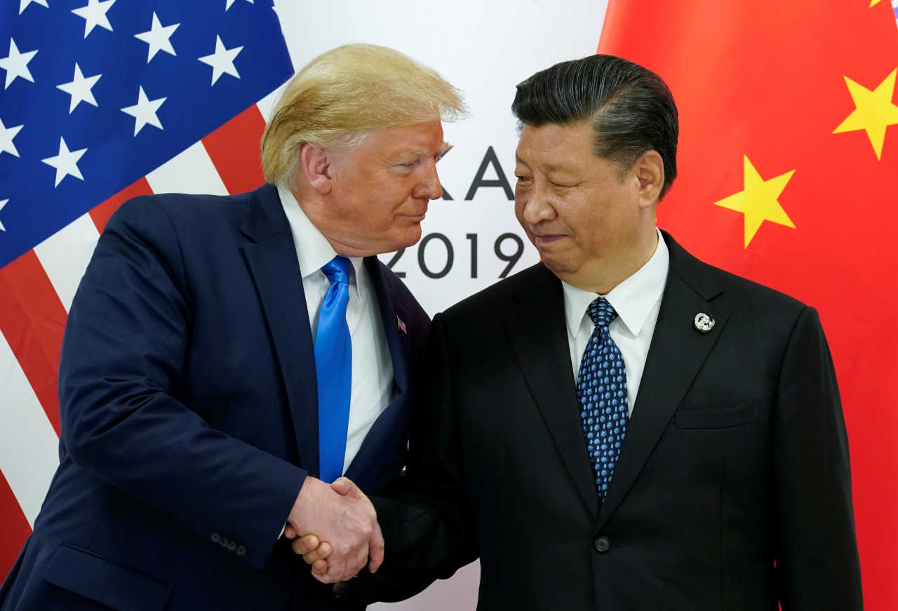 US President Donald Trump and Chinese counterpart Xi Jinping shake hands ahead of their bilateral meeting on Saturaday. (Yonhap)