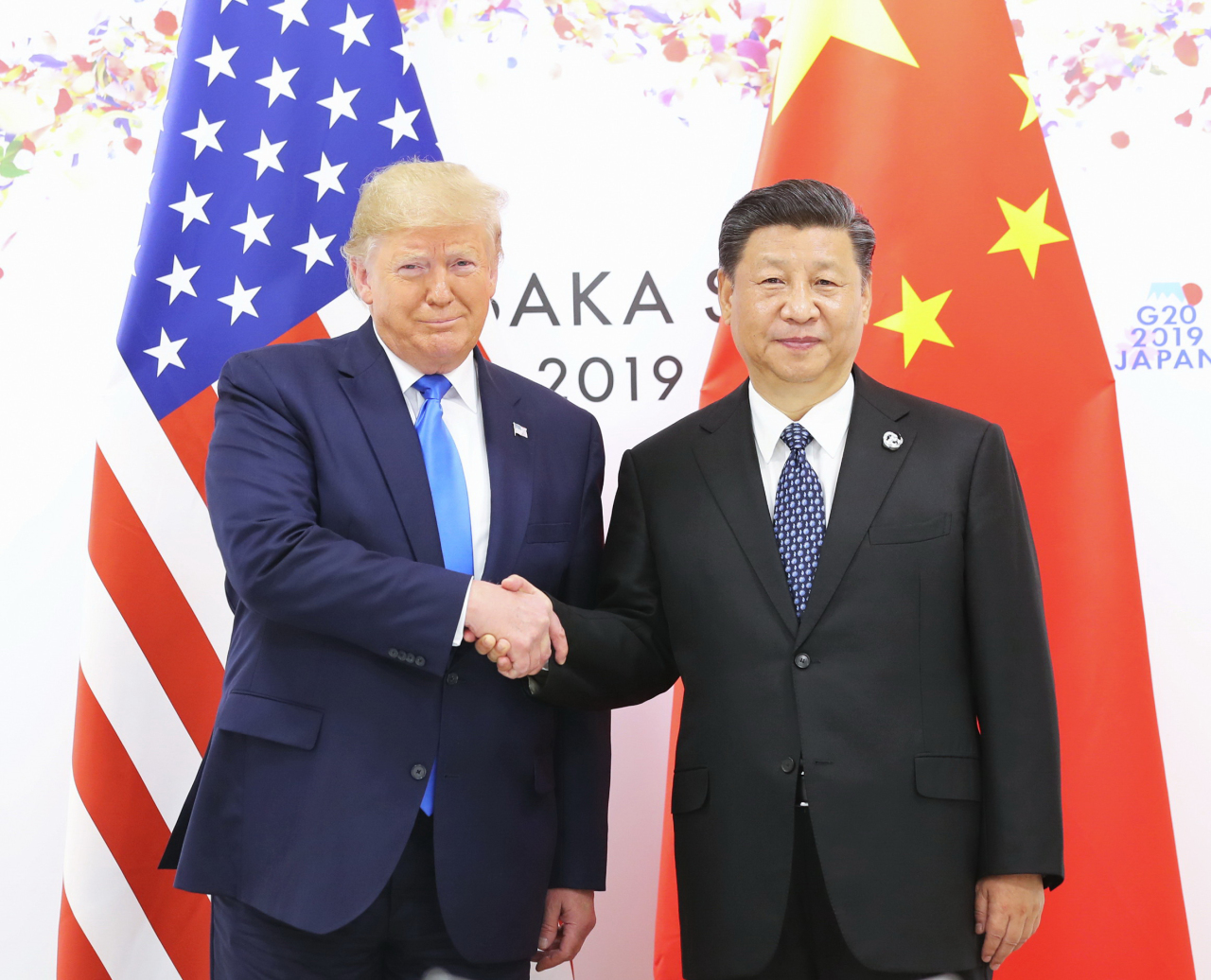 US President Donald Trump shake hands with Chinese President Xi Jinping on Saturday. (Yonhap)
