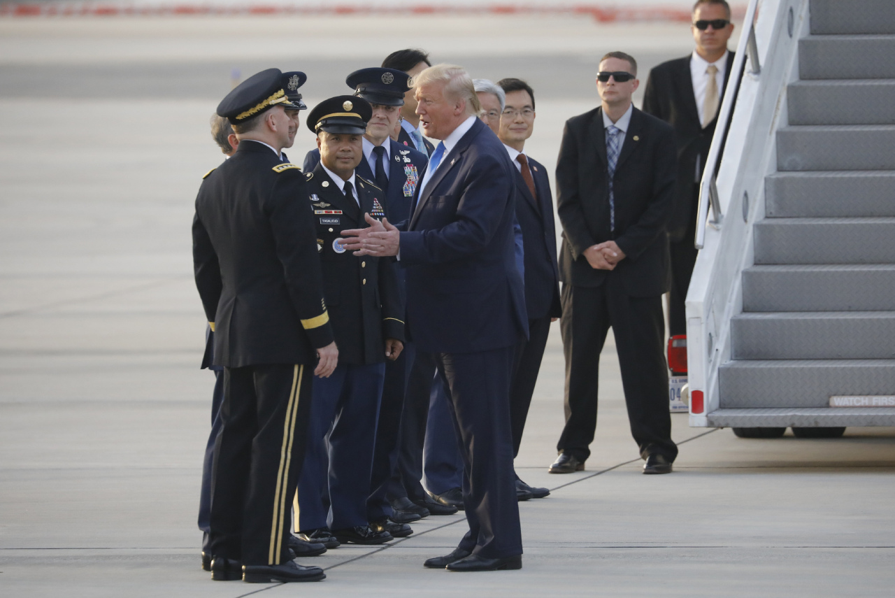 US President Donald Trump talks with a military official upon his arrival at Osan Air Base. (AP)