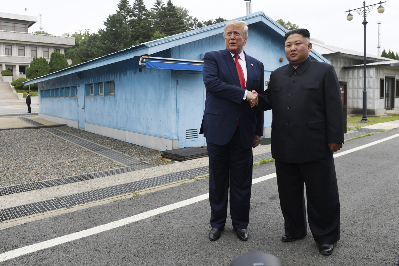 US President Donald Trump meets with North Korean leader Kim Jong Un at the border village of Panmunjom in the Demilitarized Zone, South Korea, Sunday. (AP-Yonhap)