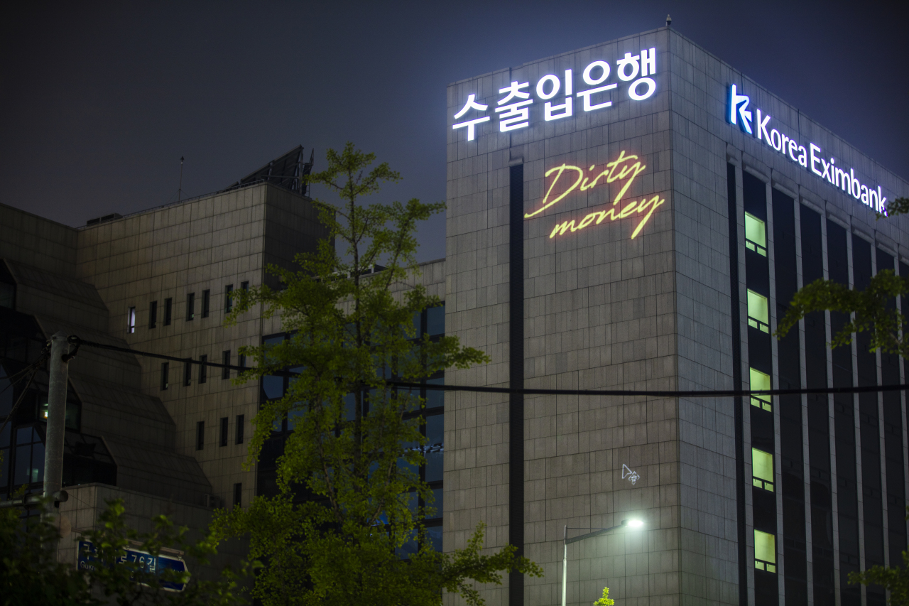 """Greenpeace Korea shines a laser light on the headquarters building of the Export-Import Bank of Korea in Seoul on Sunday, displaying messages that read, """"Dirty Money,"""" to call on Eximbank to boycott coal finance. (Greenpeace)"""