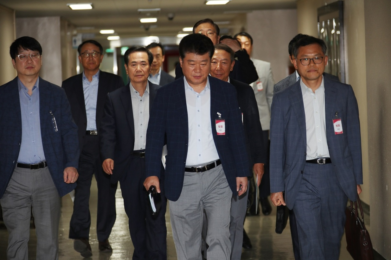 Representatives of Korean semiconductor and display industries walk to a meeting with Trade Ministry officials at the central government complex in Seoul on Monday. (Yonhap)
