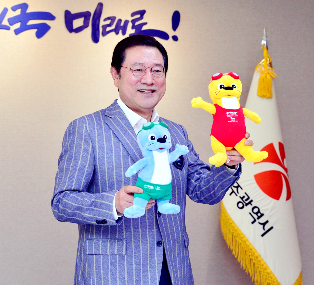 Gwangju Mayor Lee Yong-sup poses with mascots for the 18th FINA World Championships Gwangju 2019 before an interview with The Korea Herald at the Gwangju Metropolitan City Hall on Tuesday. (Park Hyun-koo/The Korea Herald)