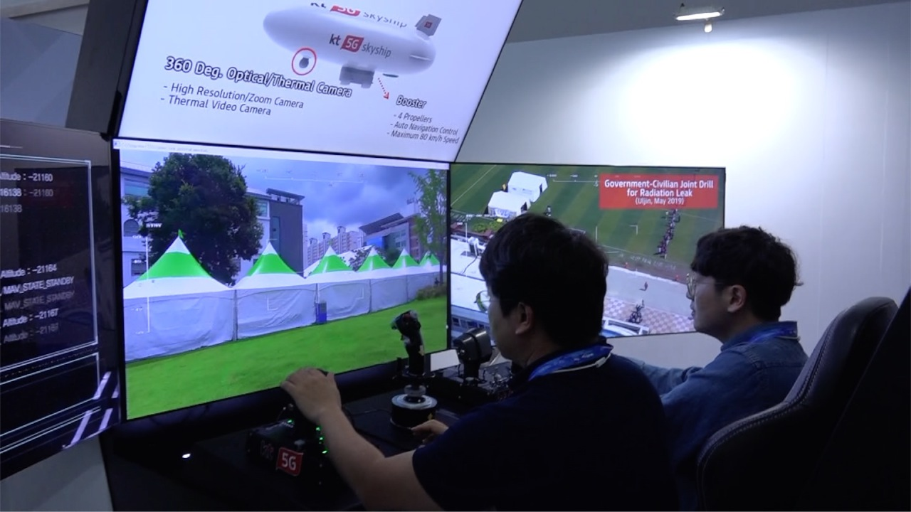Engineers from telecom firm KT monitor a smart flight cockpit connected to network airship Skyship at an ICT showroom set up at the arena complex for the 2019 FINA World Aquatics Championships in Gwangju City, Friday. (Kim Young-won / The Korea Herald)
