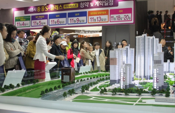 People gather around a miniature of an apartment complex, to be built in Sejong. (Jungheung Construction)