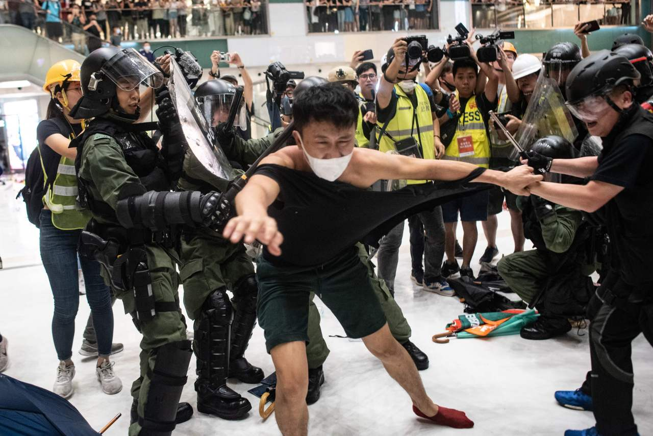 Police officers tear the shirt of a protester during a clash inside a shopping arcade in Sha Tin of Hong Kong after a rally against a controversial extradition law proposal in Sha Tin district of Hong Kong on July 14, 2019.(AFP)