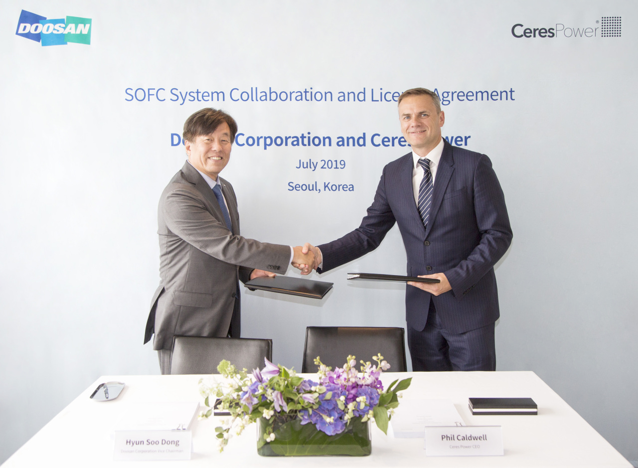 Dong Hyun-soo, vice chairman of Doosan Corp. (left), and Phil Caldwell, CEO of Ceres Power, shake hands at a collaboration and licensing agreement ceremony held in Seoul on Monday. (Doosan Corp.)