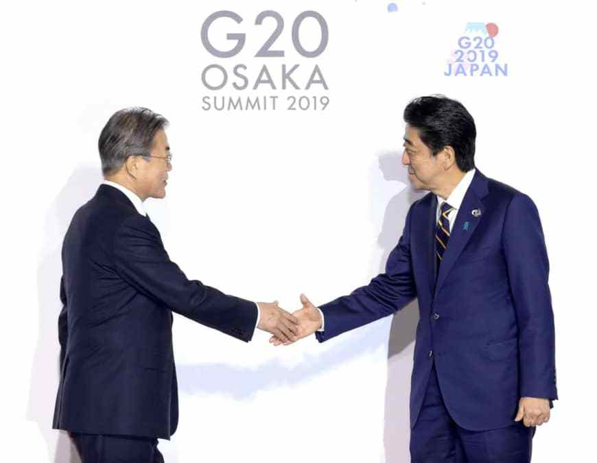 Japanese Prime Minister Shinzo Abe greets South Korean President Moon Jae-in during the Group of 20 summit in Osaka, June 28. (Yonhap)
