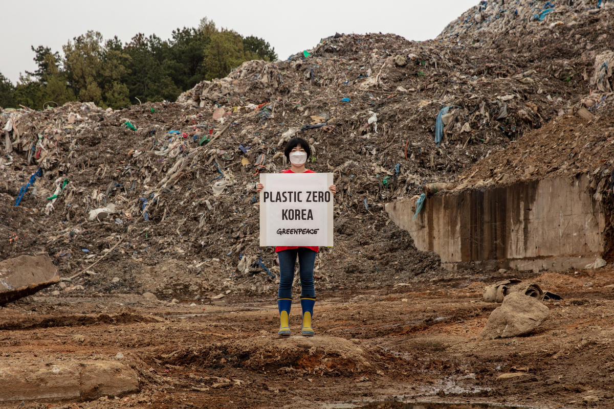 A campaigner from Greenpeace Korea stages a one-person protest in front of a mountain of garbage. (Greenpeace Korea)