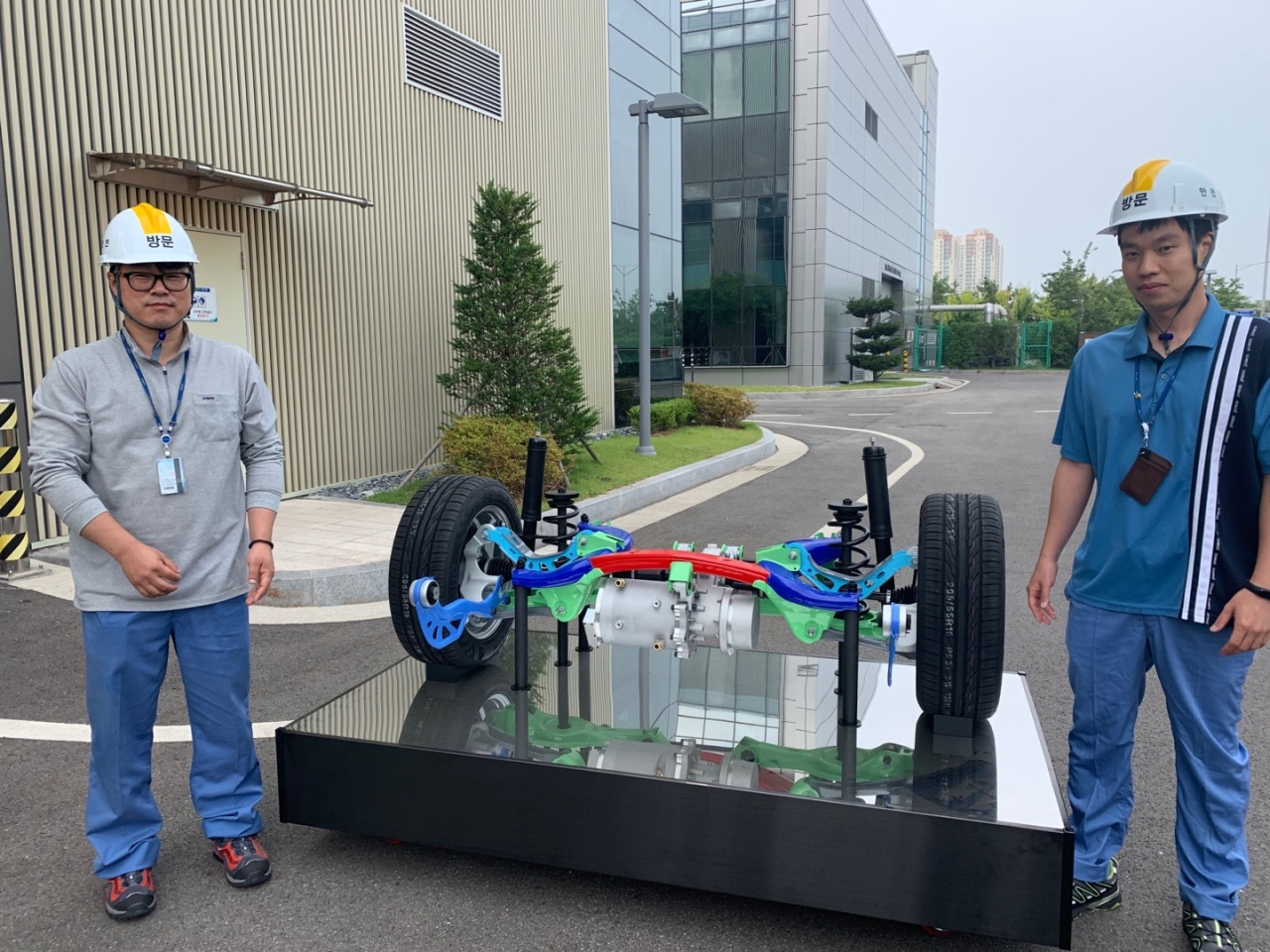 Lee Hong-woo (left), principal researcher at department materials forming research group of Posco Global R&D center, poses with suspension parts prototype his team developed in use of giga steel. (Cho Chung-un/The Korea Herald)